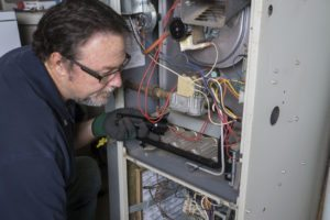 45992245 - technician looking over a gas furnace with a flashlight before cleaning it.