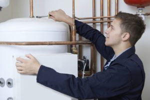 46635046 - male plumber working on central heating boiler